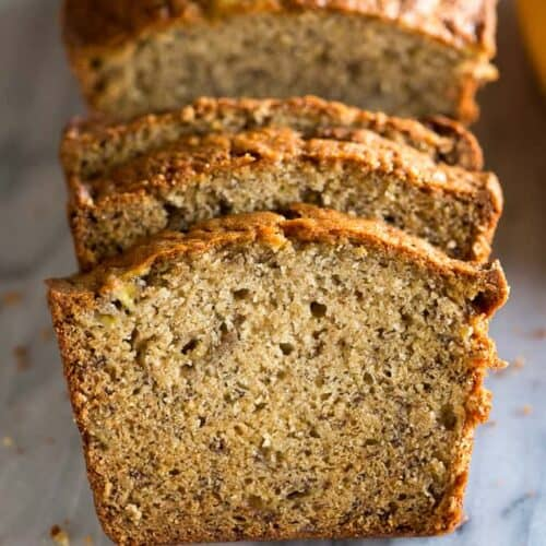 A loaf of banana bread with a few slices cut.