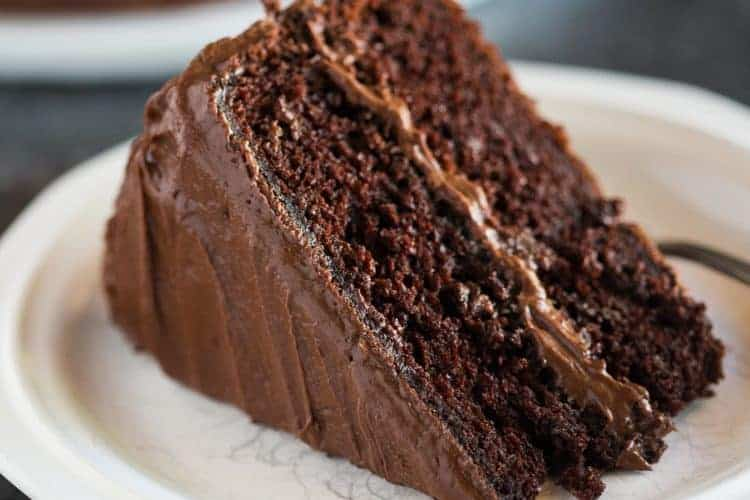 A slice of Hershey's perfectly chocolate chocolate cake, with chocolate frosting, on a white plate with a chocolate cake in the background.