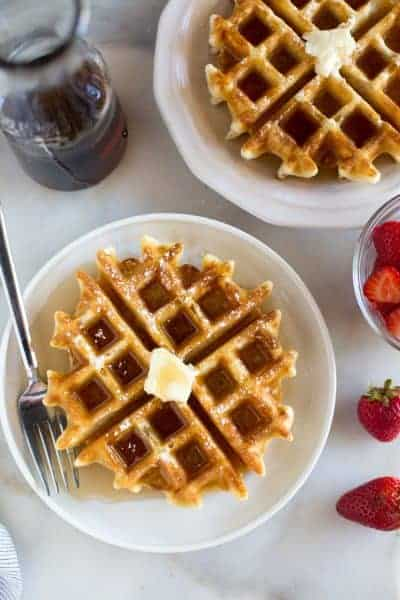 Overhead photo of two plates with Belgian waffles on them, a small bowl of strawberries and pitcher of syrup.