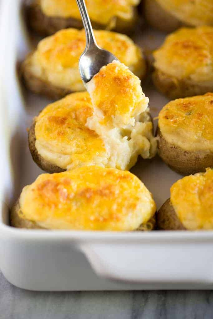 Twice baked potatoes in a baking dish and a soon scooping into one of the potatoes.