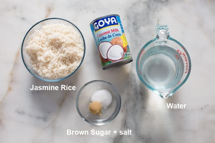 The ingredients for coconut rice including a can of coconut milk, bowl of jasmine rice, bowl with brown sugar and salt and measuring cup with water.