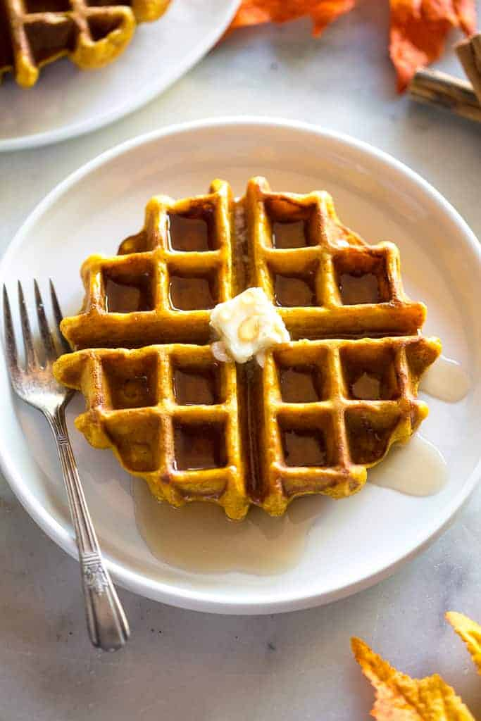 A pumpkin waffle with a syrup and a slice of butter on top, on a white plate with a fork, fall leaves and another plate of waffles to the side.