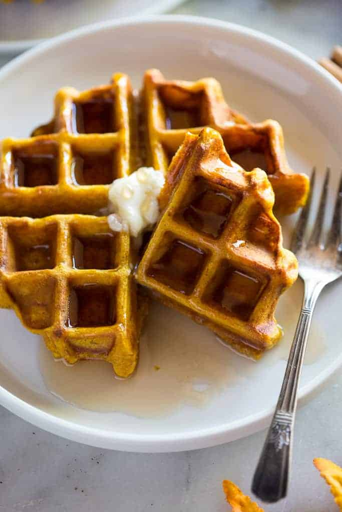 A whole pumpkin waffle with one of the four sections take off and resting at an angle, on a plate with a fork.