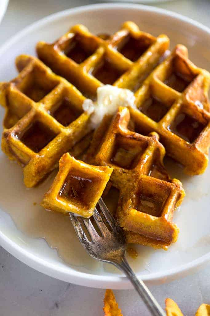 A pumpkin waffle with syrup and butter on top on a white plate with a piece divided off with a fork.