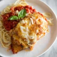 Chicken Parmesan served over spaghetti noodles with marinara sauce on a white plate, on a white marble board.