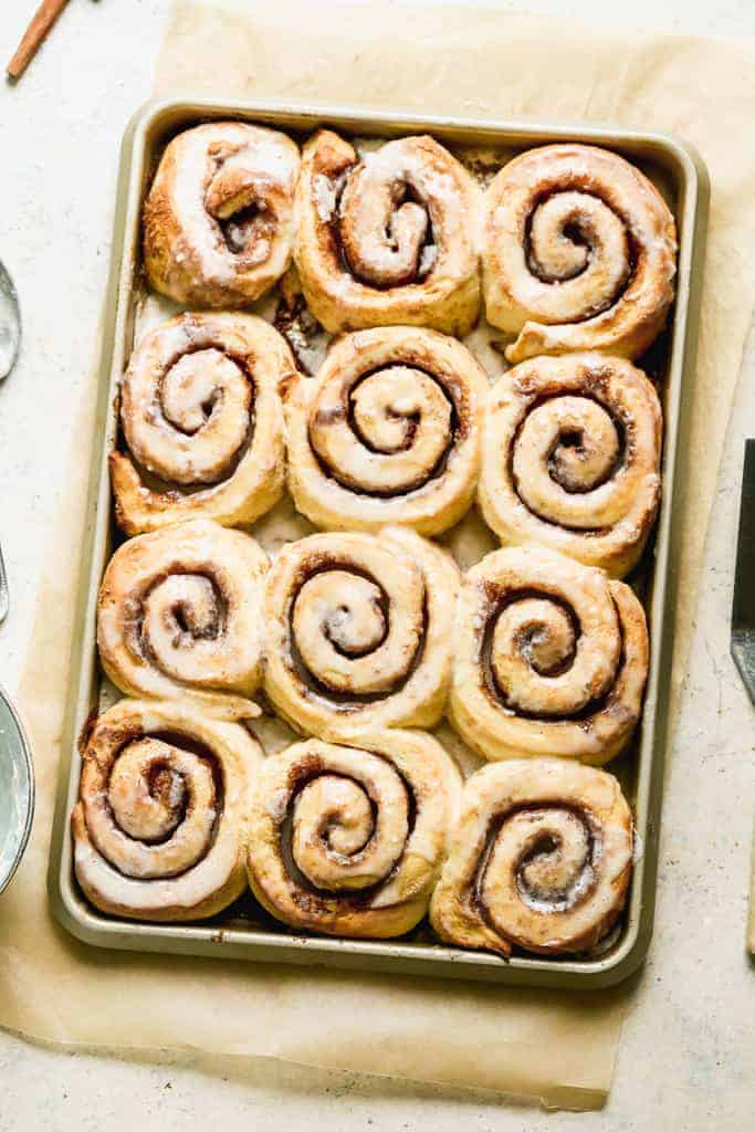 A sheet pan with 12 freshly baked cinnamon rolls with glaze on top.