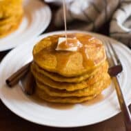 A stack of pumpkin pancakes on a white plate.