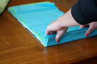 Stacked sheets of tissue paper being folded into a 1 inch strip