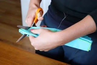 Hands holding tissue paper and scissors and making a cut into the tissue paper.