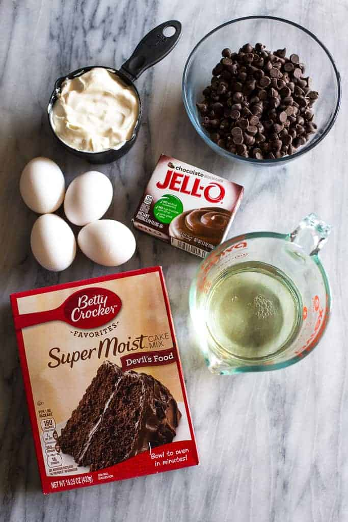 Overhead photo of the ingredients to make a chocolate nothing bundt cake, including cake mix, eggs, oil, chocolate pudding mix, sour cream and a bowl of chocolate chips.