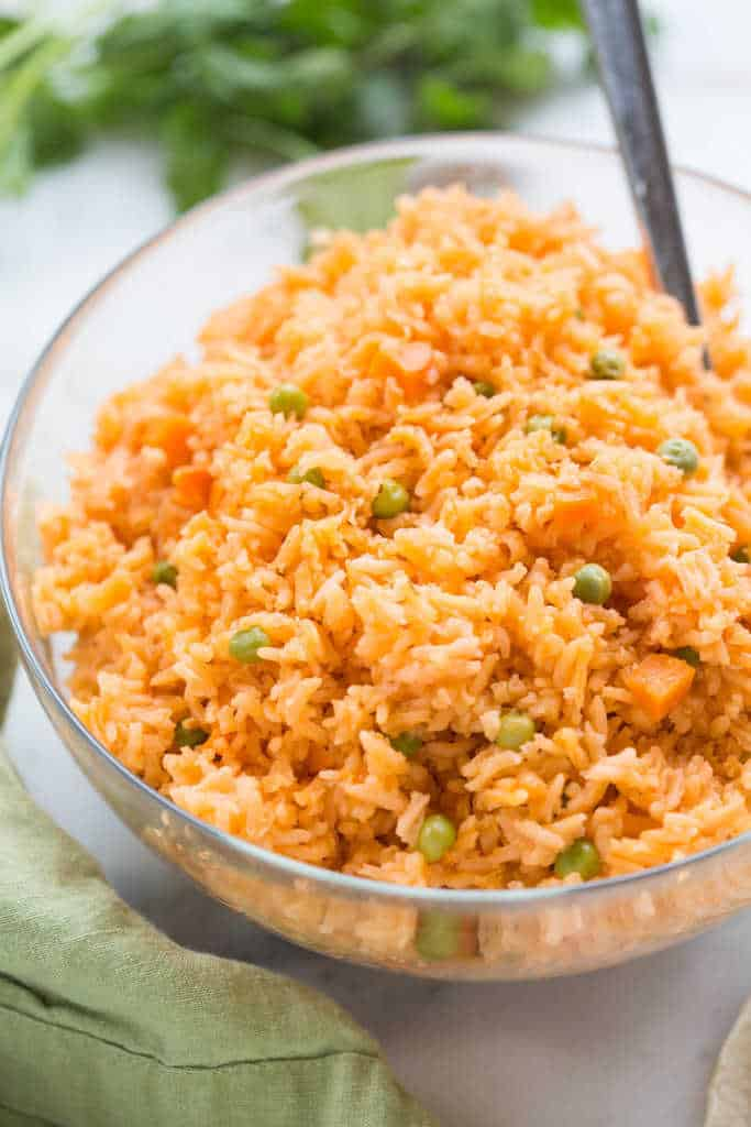 A clear glass bowl filled with orange colored Mexican rice with peas and carrots.