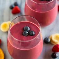 Two clear glass cups filled with a healthy breakfast smoothie with three blueberries placed on top and extra fruit in the background.