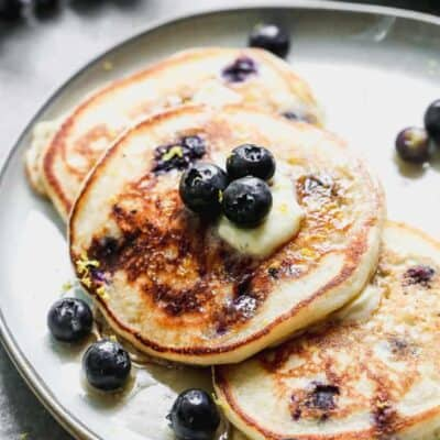 Three blueberry pancakes on a plate, with a slab of butter on top, and fresh blueberries.