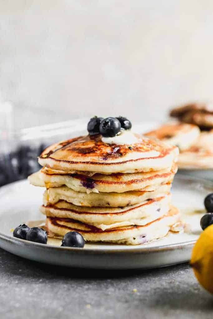 Five blueberry pancakes stacked on a plate, topped with butter, syrup and fresh blueberries.