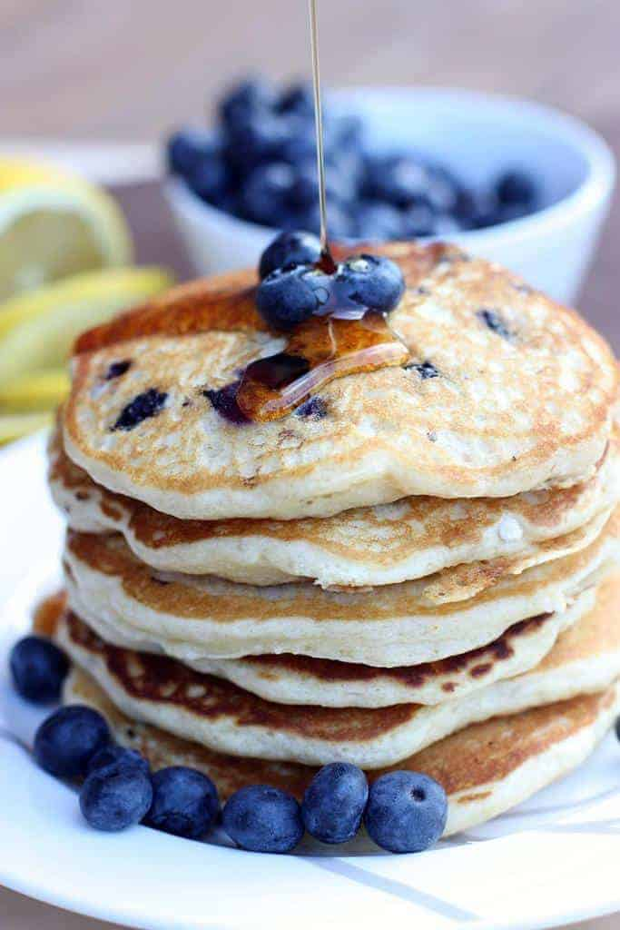 A stack of pancakes with fresh blueberries and syrup being drizzled on top.
