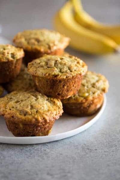 Banana Bran Muffins stacked on a white plate with bananas in the background.