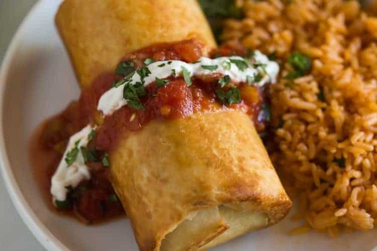 Chicken chimichanga topped with salsa, sour cream and chopped cilantro with a side of Mexican rice.