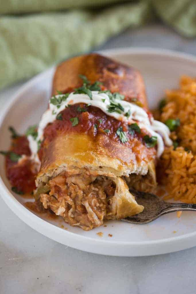 Chicken chimichanga on a plate with a fork cutting into it.