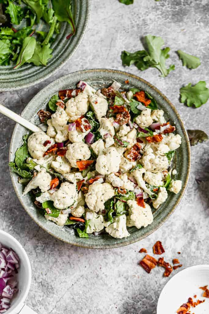 Cauliflower Salad made with raw cauliflower and cooked bacon, served in a bowl.