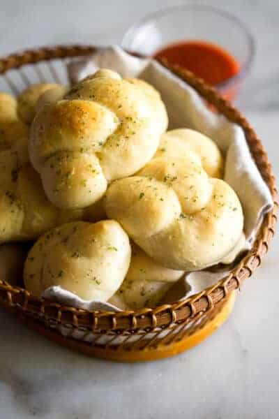 Garlic knots in a napkin-lined basket with a bowl of marinara sauce in the background.