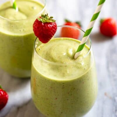 Green smoothie in two cups with a straw and strawberry on the edge of the cups.