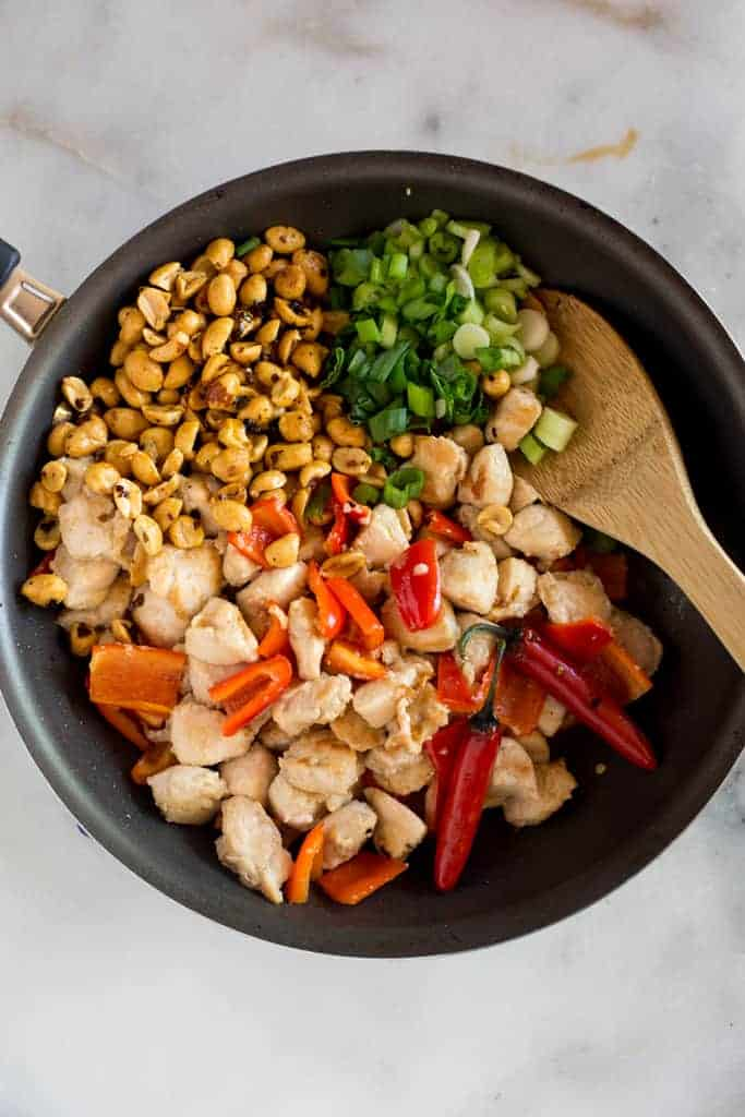 A skillet with the ingredients for kung pao chicken, including chopped chicken, green onions, peanuts and bell pepper.