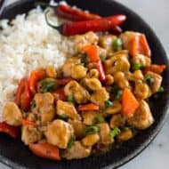 Kung pao chicken served on a black plate with white rice and chopsticks.