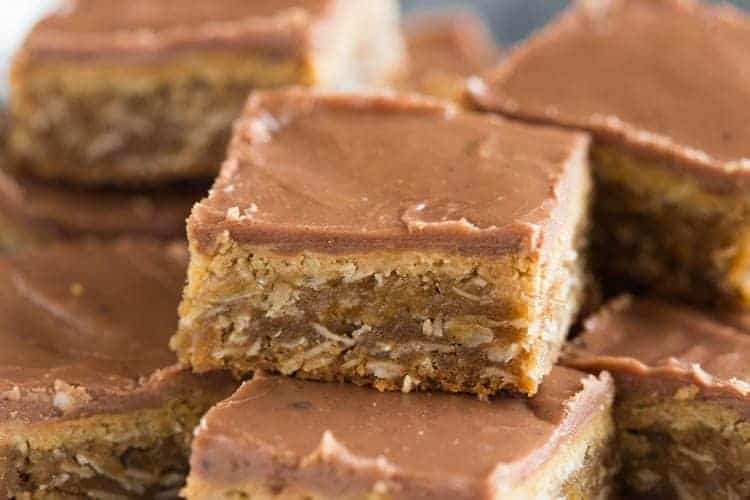 A plate full of the world's BEST peanut butter bars. Thick and chewy, with layers of smooth peanut butter and chocolate frosting.