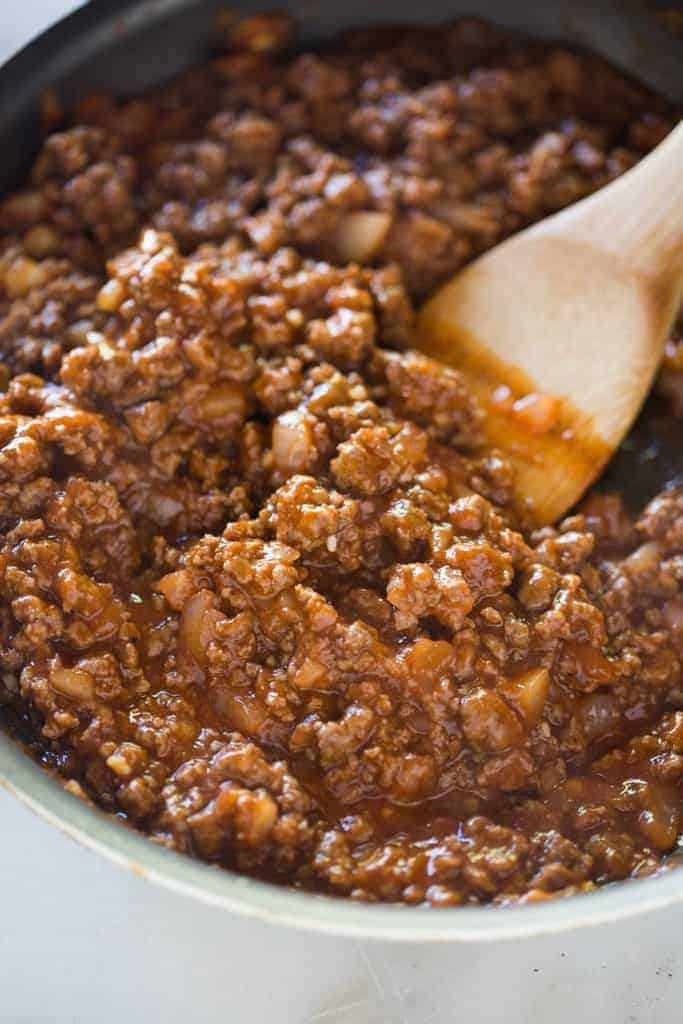 A skillet filled with the sauce for sloppy joes with a wooden spoon in it.