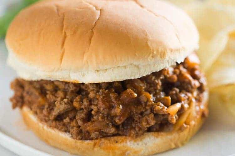 Delcious sloppy joes recipe served inside a soft hamburger bun, with a side of potato chips and salad.