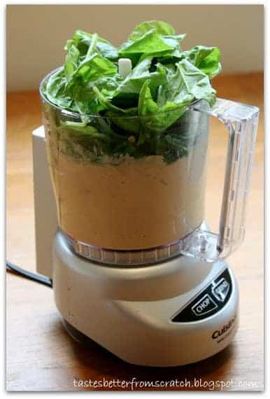 A food processor filled with ingredients to make spinach hummus.