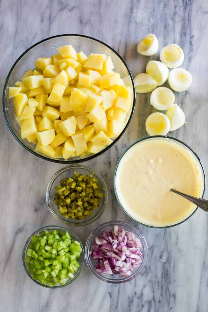 The ingredients for potato salad included diced cooked potatoes in a bowl, hard-boiled eggs, diced celery, onion, pickles and potato salad dressing.
