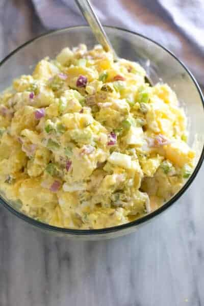Potato salad served in a clear glass serving bowl with a spoon.