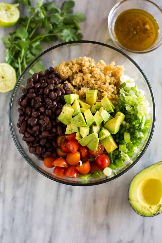 Overhead photo of a bowl with the ingredients for quinoa salad, including cooked quinoa, chopped avocado, black beans, tomatoes, onion and dressing on the side.