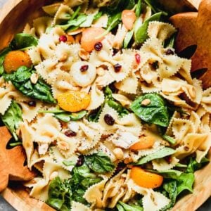 Teriyaki Pasta Salad served in a large wood bowl with wooden tongs.