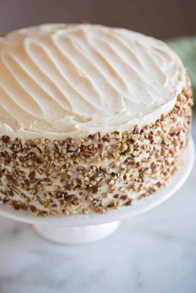 A carrot cake with pecan nuts crushed and placed around the outside of the cake.