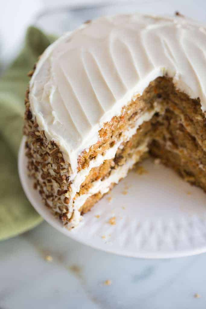 A carrot cake with cream cheese frosting with a large pieces removed.