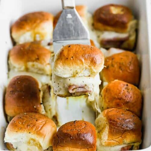 A spatula lifting a baked ham and cheese slider out of a white baking dish filled with sliders.