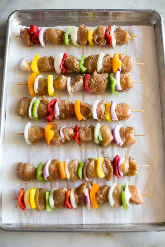 A sheet pan lined with chicken kebabs ready to be grilled.