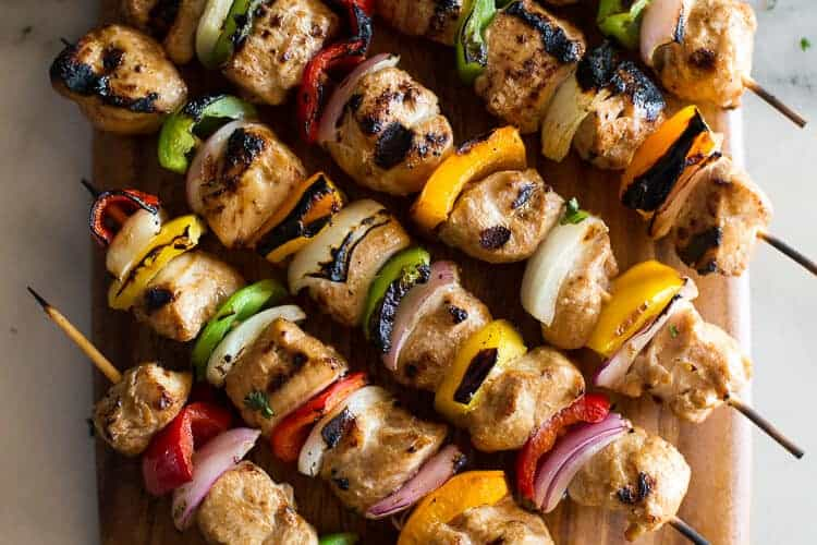 Six chicken kebabs on bamboo skewers with bell pepper and onion, served on a wood board.