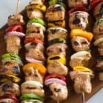 Chicken kebabs on bamboo skewers with yellow, red, and green bell pepper chunks and purple onion.
