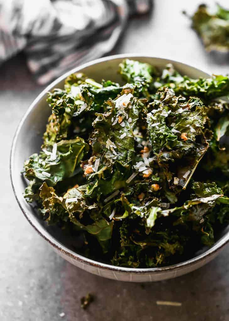 Kale chips in a bowl with a hand towel in the background.