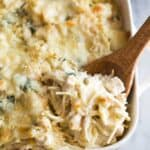 Chicken tetrazzini baked in a white casserole dish with a wooden spoon about to scoop out a serving.