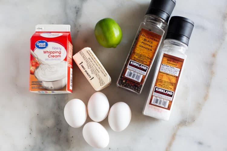 Overhead view of the ingredients needed for hollandaise sauce including butter, eggs, cream, lime juice, salt and pepper.
