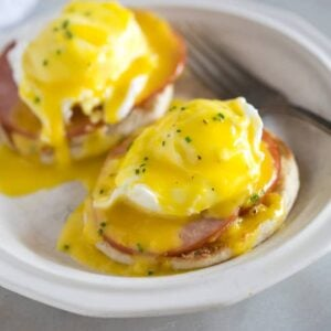 A plate with two eggs benedict which includes english muffin topped with a slice of canadian bacon, poached eggs and homemade hollandaise sauce.