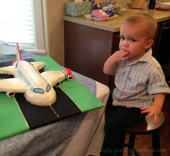 A little boy looking at a airplane cake on a board designed as a runway.