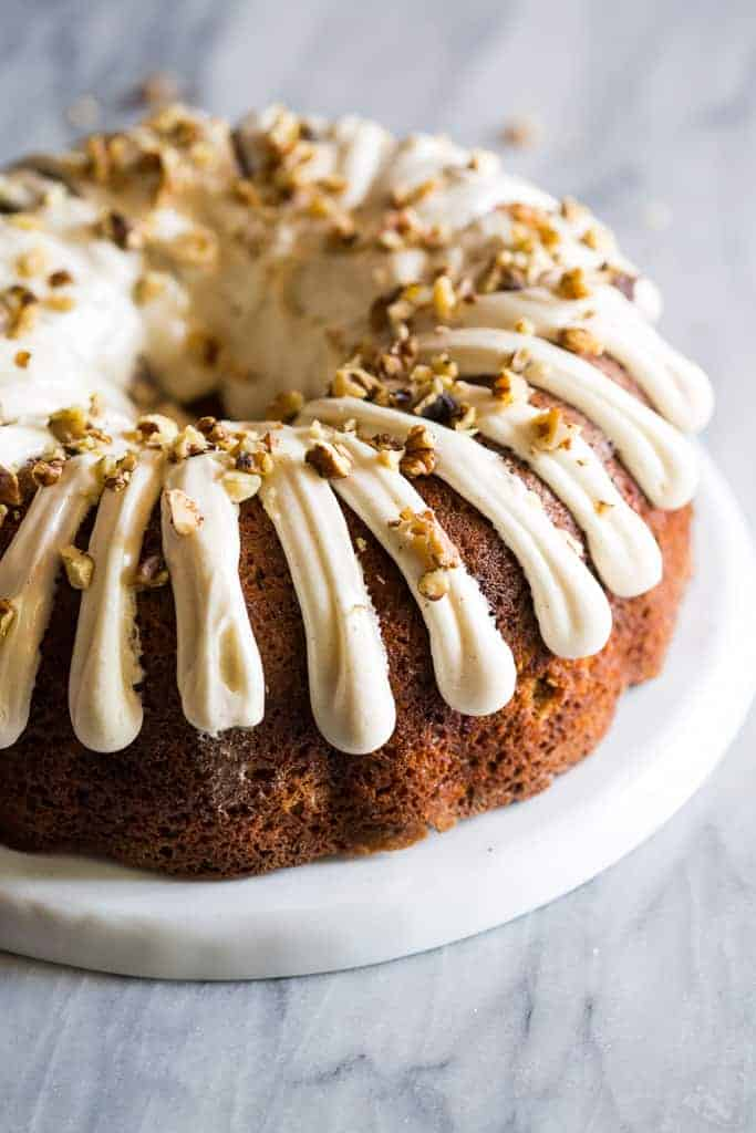 A banana bundt cake with cream cheese frosting and walnuts sprinkled on top, served on a white plate.