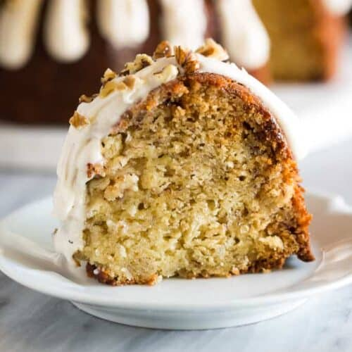 A standing slice of banana bundt cake on a small white plate with the whole cake in the background.
