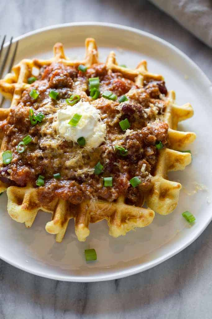 Close up photo of a waffles with chili, sour cream and chopped green onions on it.