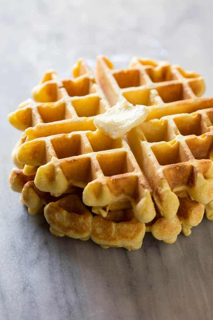 Two cornbread waffles stacked on each other on a white marble board with a piece of butter on top.